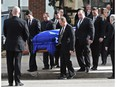 Pallbearers carry the casket of former Premier Don Getty draped in the Alberta flag to the hearse as family members follow after his state funeral at All Saints Anglican Cathedral in downtown Edmonton, March 5, 2016.