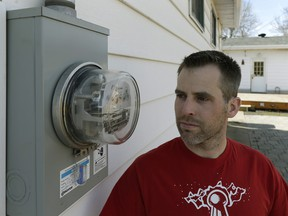 Mike Thomas beside his power meter at his home in northeast Edmonton. He's concerned that the contractor for Epcor is not using electricians to replace existing meters with advanced devices.