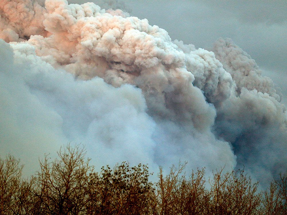A plume of smoke from a wildfire near Fort McMurray Alberta is lit up at sunset on May 4, 2016. A wildfire has forced the evacuation of Fort McMurray, the fourth largest city in Alberta.