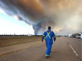 A man wearing fire retardant clothing walks up to a road block on Highway 63 as smoke rises from a forest fire near Fort McMurray, Alberta on May 6, 2016.