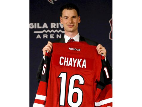 Newly appointed Arizona Coyotes general manager John Chayka holds a game jersey after a news conference announcing his promotion, Thursday, May 5, 2016, in Glendale, Ariz. Chayka is the youngest GM in NHL history.