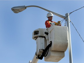 Joel Kwasny works to put in temporary overhead power to a light standard near the corner of 106A avenue and 65 Street. Upgrading light standards is a key part of Edmonton's plan to reduce greenhouse gas emissions.