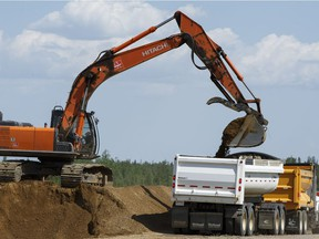 Construction crews work in the median of Highway 63 near Fort McMurray, Alta., on Tuesday June 7, 2016. The now twinned highway was the lifeline for people fleeing the massive wildfire.