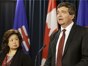 Alberta's Agriculture and Forestry Minister Oneil Carlier (right) and Bev Yee, AFSC's interim chairwoman, speak about the dismissal of the board of directors of the Agriculture Financial Services Corportation during a press conference at the Alberta Legislature on June 13, 2016.