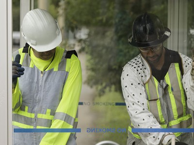 Edmonton Transit System utility workers Robert Young (left) and Pono Vey replace a broken glass panel at a bus shop on 107 Avenue near 120 Street in Edmonton, on Wednesday, July 20, 2016.