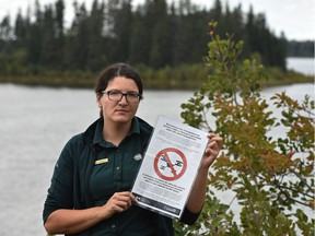 Janelle Lane, Elk Island National Park, communications officer, shows a sign on Sept. 12, 2016 informing national park visitors that drones are banned to protect the sensitive environment.