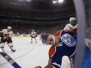The Edmonton Oilers' Drake Caggiula (36) collides with Calgary Flames' Nicklas Grossman (8) during first period pre-season NHL action at Rogers Place, in Edmonton on Monday Sept. 26, 2016.