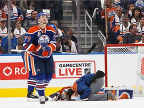 A trainer checks on goalie Jonas Gustavsson #50 of the Edmonton Oilers during a game against the Buffalo Sabres on October 16, 2016 at Rogers Place in Edmonton.