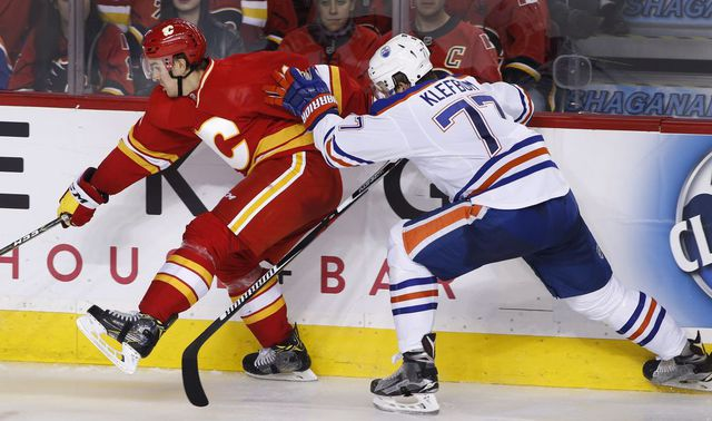 Edmonton Oilers' Oscar Klefbom, right, from Sweden, battles with Calgary Flames' Mikael Backlund, from Sweden, during third period NHL action in Calgary, Alta., Friday Oct. 14, 2016.