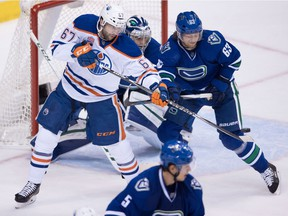 Edmonton Oilers' Benoit Pouliot, left, tips the puck in front of Vancouver Canucks' Philip Larsen, of Denmark, but is stopped by goalie Ryan Miller, back, during the second period of an NHL hockey game in Vancouver, B.C., on Friday October 28, 2016.