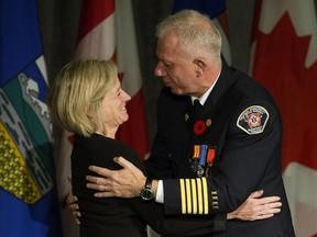 Premier Rachel Notley embraces Fort McMurray fire Chief Darby Allen during a ceremony to recognize the heroes of the Fort McMurray wildfire at the Alberta legislature, in Edmonton on Monday, Oct. 31, 2016.