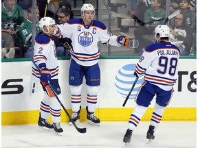 Edmonton Oilers' Andrej Sekera (2) and Jesse Puljujarvi (98) celebrate with Connor McDavid after McDavid scored in the third period against the Dallas Stars on Saturday, Nov. 19, 2016, in Dallas.