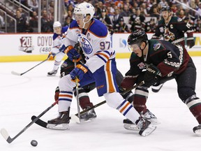 Edmonton Oilers center Connor McDavid (97) tries to skate past Arizona Coyotes defenseman Connor Murphy (5) during the first period of an NHL hockey game Friday, Nov. 25, 2016, in Glendale, Ariz.