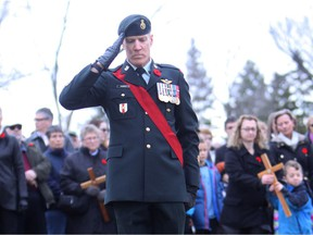 Master Warrant Officer Marco Favasoli places a cross in the ground for fellow Canadian Forces soldier Master Cpl. Erin Doyle, a soldier with the Princess Patricia's 3rd Battalion who died in August 2011 in Afghanistan, during a Remembrance Day Event at the Ainsworth Dyer Bridge in Edmonton's Rundle Park, Nov. 11, 2016.