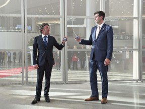 Edmonton Oilers owner Daryl Katz, left, and Edmonton Mayor Don Iveson prepare to pull the banner down during the opening ceremony at Rogers Place, the new home of the Edmonton Oilers, in Edmonton, on Sept. 8, 2016.