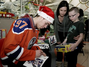 Edmonton Oilers captain Connor McDavid autographs a photo for Stollery Children's Hospital patient Luca Flynn, 8, and his mother Jennifer. McDavid and other members of the team made their annual visit to the hospital on December 15, 2016.