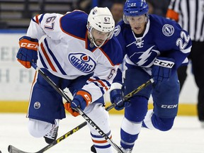 Benoit Pouliot of the Edmonton Oilers avoids a check from Erik Condra of the Tampa Bay Lightning at the Amalie Arena on Jan. 19, 2016 in Tampa, Fla. (File)