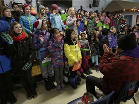 Students from George H. Luck School sing Christmas carols for patrons of the Boyle Street Community Services after delivering hundreds of backpacks to the centre on December 19, 2016. The backpacks will be distributed to the homeless and people in need.