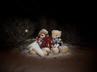 Two teddy bears in hockey jerseys sit outside the Whitecourt , Alta home of Radek MacDougall and Ryder MacDougall, Tuesday Dec. 20, 2016. The two boys were were found dead in their Spruce Grove home on Monday Dec. 19, 2016.