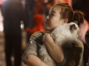 An evacuee holds her cat on the street during a fire at the Oliver Place apartment complex at 117 Street and Jasper Avenue in Edmonton on Thursday, Jan. 19, 2017. Five hundred people were evacuated in the two alarm fire.