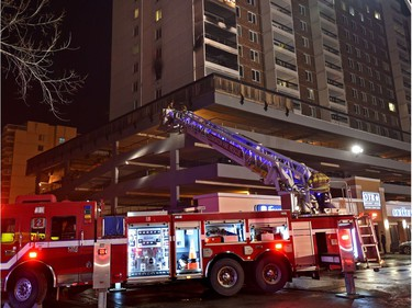 Firefighters use the aerial ladder to access the top of the parkade were above them fire caused damage to a number of suites to an apartment complex on Jasper Ave. and 118 St. in Edmonton, Thursday, Jan. 19, 2017.