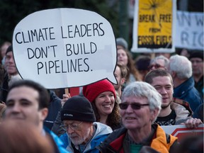 A woman holds a sign during a protest and march against the Kinder Morgan Trans Mountain Pipeline expansion, in Vancouver, B.C., on Saturday Nov. 19, 2016.