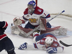 Edmonton Oil Kings goalie Patrick Dea makes a save against the Regina Pats as teammate Riley Stadel slides into him during WHL action against the Regina Pats on Feb. 10, 2017, at Edmonton's Rogers Place.