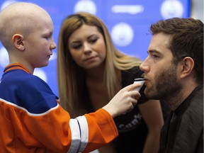 Edmonton Oilers defenceman Eric Gryba has his beard shaved by Ethan Hughes, 10, for charity, at Rogers Place in Edmonton Wednesday Feb. 15, 2017. Gryba was raising awareness for Garth Brooks' Teammates for Kids Foundation. Helping Ethan is Farrah Hart from Tommy Gun's Original Barbershop.