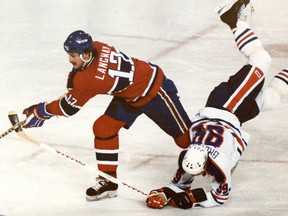 Wayne Gretzky takes a spill going for the puck against Rod Langway of the Montreal Canadiens in January 1981.