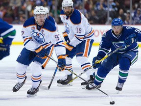 Edmonton Oilers' Connor McDavid (97) skates with the puck while being chased by Vancouver Canucks' Alex Biega (55) during first period NHL hockey action in Vancouver, B.C., on Saturday, April 8, 2017.