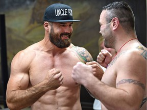 Former Edmonton Eskimos player Adam Braidwood, left, faces off with opponent Tim Hague after he weighs in at 250.1 lb. on June 15, 2017, at the Chateau Lacombe for his upcoming boxing match Friday in Edmonton.