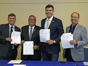 Tom Ruth, president and CEO of Edmonton International Airport, left, City of Leduc Mayor Greg Krischke, Edmonton Mayor Don Iveson and Leduc County Mayor John Whaley hold the signed annexation agreement on June 30, 2017 at Edmonton International Airport between the City of Edmonton and Leduc County.