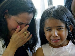 Yolanda Duarte Martinez (left) and her daughter Beverly Nicole Picon, 6, (right) break down in tears during a news conference in Edmonton on June 20, 2017. Yolanda, her husband Jilmar David Picon and oldest son Edisson Esmith Picon, 23, are being deported to Guatemala, where they fear for their lives. The other four children will return to the U.S., where they have citizenship, to live with a relative.