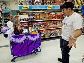 """Sadie Martin, 10, and her father Mark Martin react after finishing their three-minute shopping spree through Toys """"R"""" Us, 3940 Gateway Blvd., in Edmonton on Tuesday, Sept. 26, 2017."""