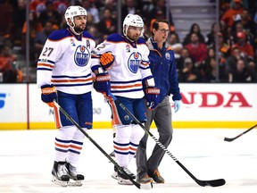 Andrej Sekera #2 of the Edmonton Oilers is helped off the ice by Milan Lucic #27 and a trainer during the first period against the Anaheim Ducks in Game Five of the Western Conference Second Round during the 2017 NHL Stanley Cup Playoffs at Honda Center on May 5, 2017 in Anaheim, California.