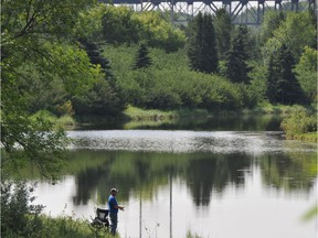 A fisherman stands near the shore of a pond in Hermitage Park in a file photo. The park is one of the popular features in the northeast's Ward 4.