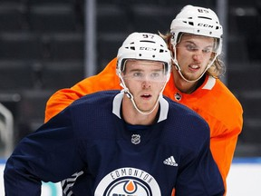 Connor McDavid, in blue, battles against William Lagesson during the Edmonton Oilers training camp at Rogers Place in Edmonton on Friday, Sept. 15, 2017.