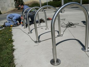 Fabricators with Edmonton's Mobile Equipment Services Branch install bike racks outside Commonwealth Stadium on May 11, 2015, in Edmonton. The city has issued a tender to purchase 120 new bike racks and responding manufacturers are asked to spell out their sustainability policy.
