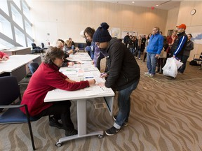 People line up to take part in advance voting in the Heritage Room at City Hall voting stations on Friday Oct. 13, 2017 in Edmonton.