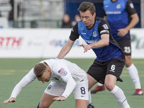 FC Edmonton's Nik Ledgerwood watches as Jacksonville Armada  Jake Black falls at Clarke Park, in Edmonton April 8, 2017.