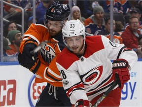 Carolina Hurricanes' Elias Lindholm (28) is chased by Edmonton Oilers' Adam Larsson (6) during NHL action on Oct. 17, 2017, in Edmonton.