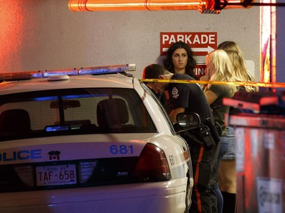 Bar patrons are interviewed by a police officer outside The Pint bar on 109 Street near Jasper Avenue following a high speed chase where several pedestrians were struck.