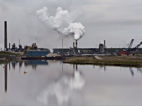 The Syncrude oil sands extraction facility is reflected in a tailings pond near the city of Fort McMurray, Alta., on June 1, 2014.