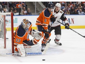 Phoenix Coyotes' Christian Dvorak (18) and Edmonton Oilers' Adam Larsson (6) battle in front as goalie Cam Talbot (33) makes the save during third period NHL action in Edmonton on Tuesday November 28, 2017.