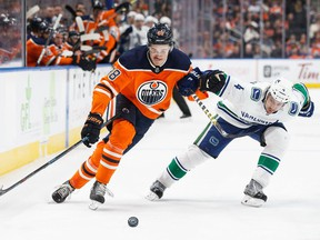 EDMONTON, AB - JANUARY 20: Jesse Puljujarvi #98 of the Edmonton Oilers battles against Michael Del Zotto #4 of the Vancouver Canucks at Rogers Place on January 20, 2018 in Edmonton, Canada.