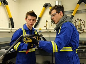 Dylan Johanson (left, 16) and Phillip Salisbury (right, also 16) are in the plumbing program at Archbishop O'Leary High School, the first Catholic school in Edmonton to offer a plumbing lab where students can begin to train for the plumbing trade.