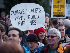 A woman holds a sign during a protest and march against the Kinder Morgan Trans Mountain Pipeline expansion, in Vancouver, B.C., on Saturday November 19, 2016. File photo.