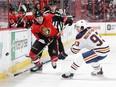 OTTAWA, ON - MARCH 22: Cody Ceci #5 of the Ottawa Senators chips the puck past Ryan Nugent-Hopkins #93 of the Edmonton Oilers in the second period at Canadian Tire Centre on March 22, 2018 in Ottawa, Ontario, Canada.