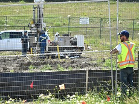 A worker installs fencing as other workers drill core samples in a contaminated parcel at the old wood treatment plant site, Domtar, where a section of unoccupied land nearby was contaminated enough that a metal fencing was erected near 43 Street and Yellowhead Trail in Edmonton on Thursday, June 28, 2018.