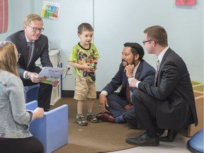 Derek Willis, five, stands with Alberta government cabinet ministers David Eggen,  left, Ricardo Miranda  and Jon Carson at the south Edmonton location of the Children's Autism Services of Edmonton on June 8, 2018. The Alberta government is providing a $1.25-million grant to support the purchase of the facility to help more than 200 families.